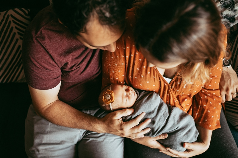 Orlando Newborn Photography, couple sitting on couch holding newborn baby girl