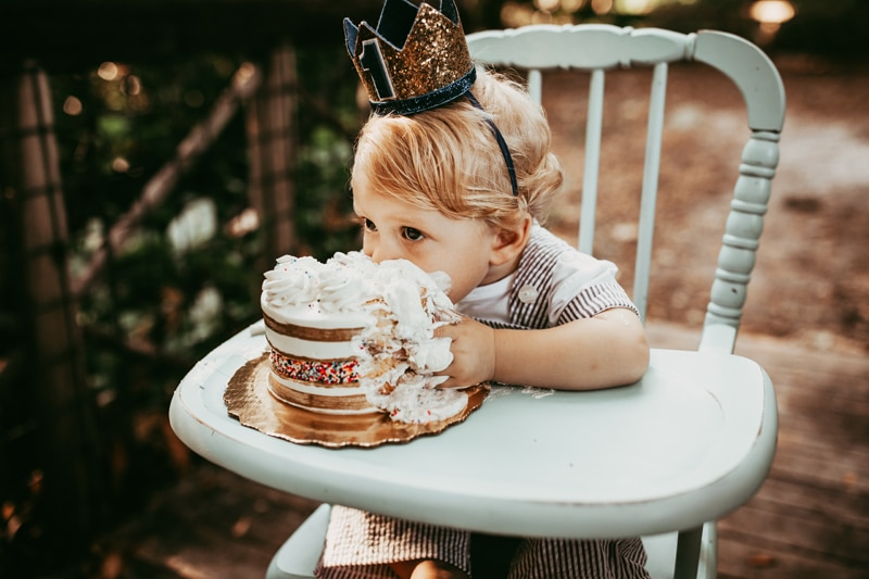 Orlando Cake Smash Photographer, little boy eating cake in highchair with crown on