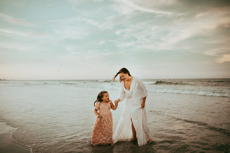 Orlando Family Photographer, mother and daughter walking through the water at beach
