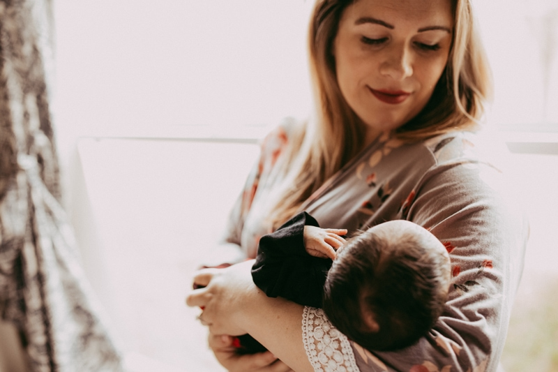 Orlando Newborn Photography, mother holding baby next to a window