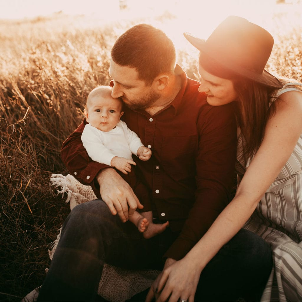 Orlando Family Photography. family of three sitting together in field