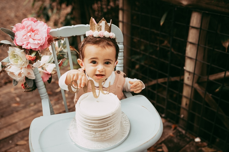 Orlando Cake Smash Photographer, little girl looking over cake in highchair