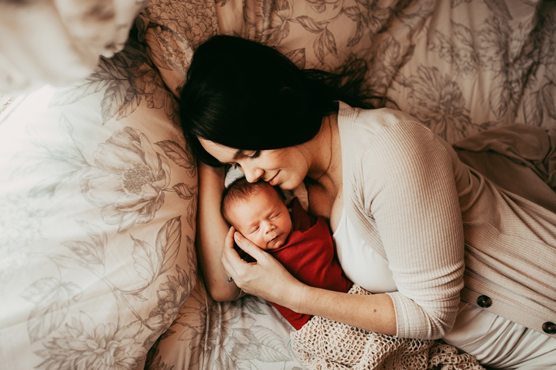 Orlando Newborn Photography, mother laying in bed cuddled up with sleeping baby