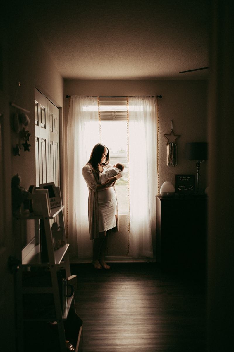 Orlando Newborn Photography, far away shot of mother holding baby next to window