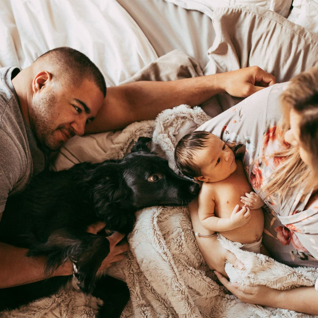 Orlando Lifestyle Newborn Photography, family of three laying in bed together with family dog