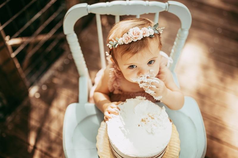 Orlando Cake Smash Photographer, little girl looking up while eating cake
