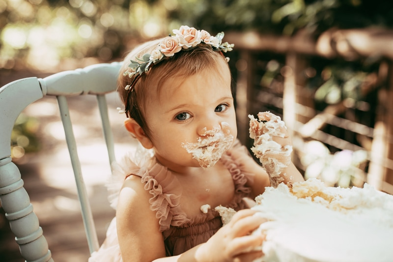 Orlando Cake Smash Photographer, little girl looking at camera with cake on her face