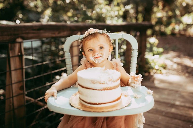 Orlando Cake Smash Photographer, little girl smiling while eating cake in highchair