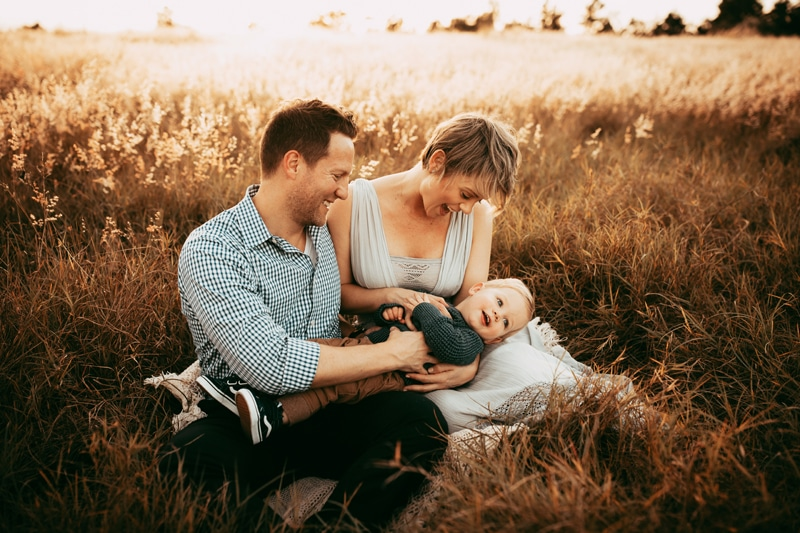 Orlando Family Photographer, family of three sitting and playing together in a field