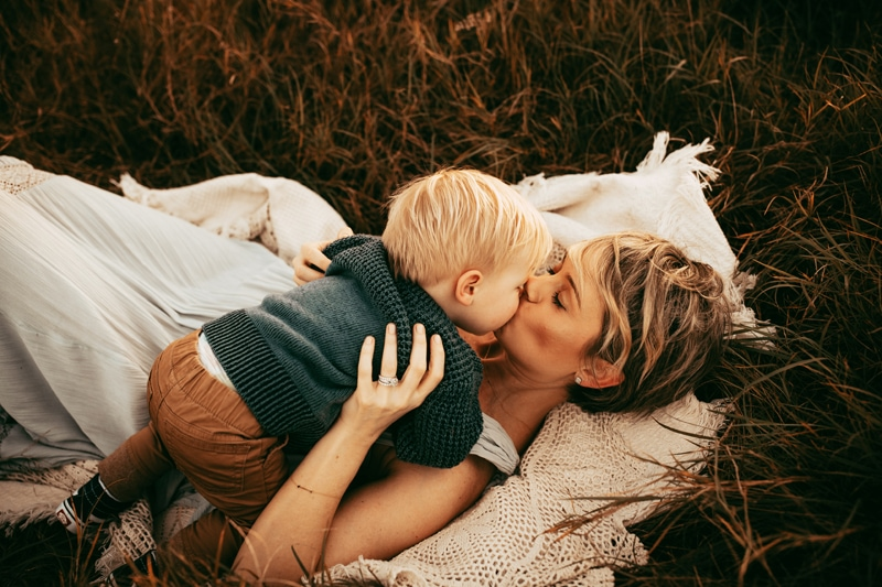 Orlando Family Photographer, mother laying in grass giving baby boy a kiss