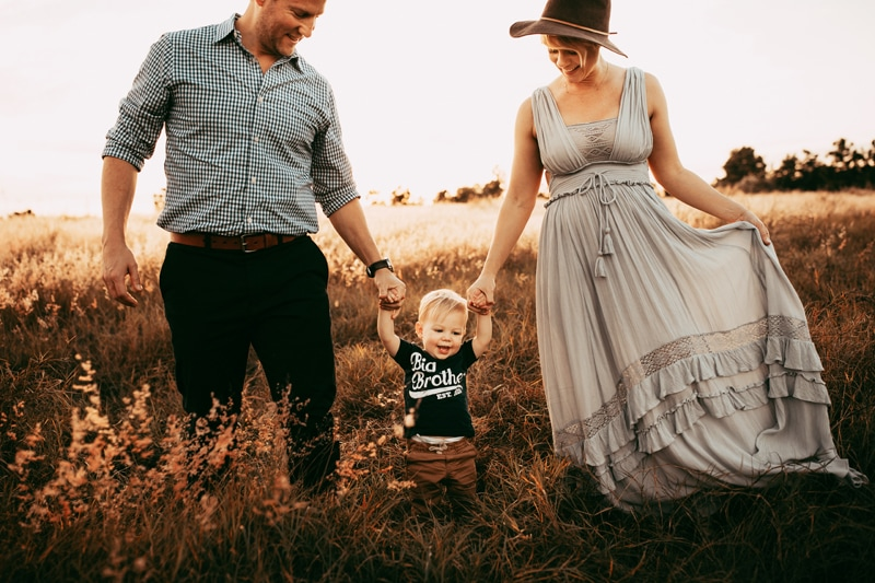 Orlando Family Photographer, close up of family of three walking in field together
