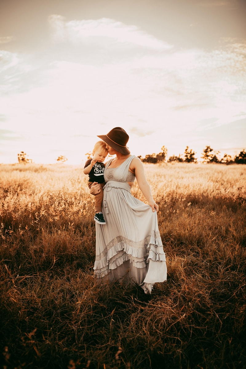 Orlando Family Photographer, mother holding son on her hip in a field