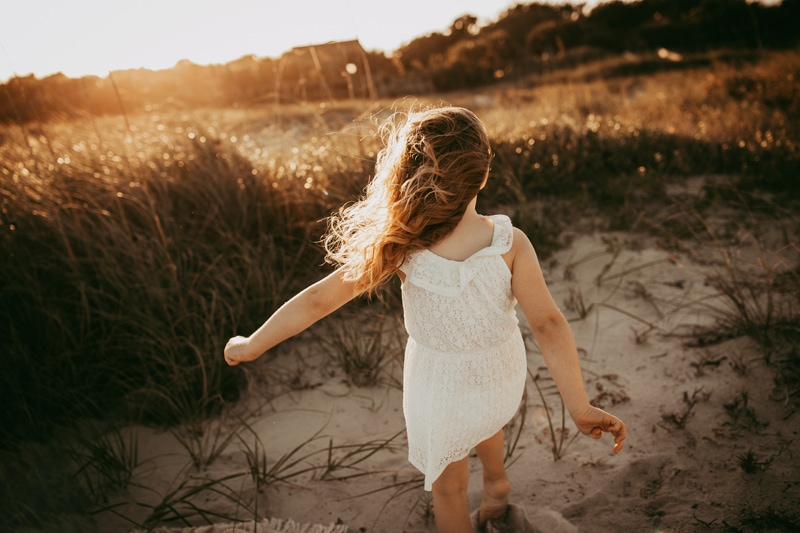 Orlando Family Photographer, young girl walking through sand with wind in her hair