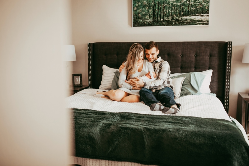 Orlando Newborn Photography, couple holding newborn baby while sitting in bed