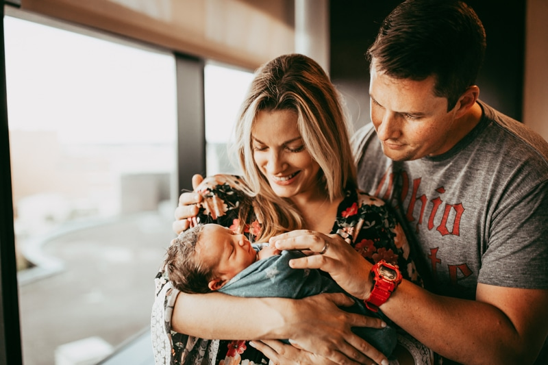 Orlando Fresh 48 Photographer, mother and father holding newborn baby next to a window